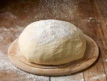 Fresh raw dough. Flour falling on fresh raw dough Stock Photos