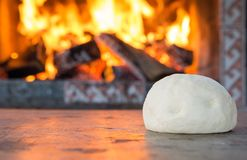 Fresh raw dough for pizza or bread baking on wooden table against the Burning fireplace. comfort mood concept. Space for text Royalty Free Stock Images