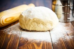 Fresh raw dough with a rolling pin. On a wooden table Stock Photography