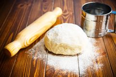 Fresh raw dough with a rolling pin. On a wooden table Royalty Free Stock Image