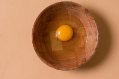 Fresh raw egg in a mixing bowl. Overhead view of a healthy fresh raw egg with a deep yellow yolk in a mixing bowl waiting to be used as an ingredient in cooking Stock Photo