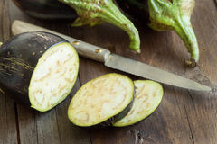 Fresh  Raw eggplants with knife. On the wood background Royalty Free Stock Image