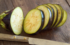 Fresh  Raw eggplants with knife. On the wood background Stock Images