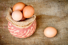 Fresh raw eggs in clay pot Stock Image