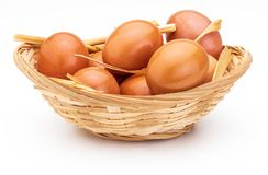 Fresh and raw eggs in wicker basket and straw. royalty free stock image