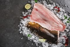 Fresh raw fillet fish and whole fish with spices on ice over dark stone background. Seafood, top view, flat lay.  royalty free stock images
