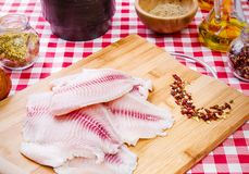 Fresh raw fillet of tilapia fish. With spices and ingredients, on the table Stock Images