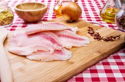 Fresh raw fillet of tilapia fish. With spices and ingredients, on the table Stock Image