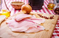 Fresh raw fillet of tilapia fish. With spices and ingredients, on the table Stock Photography