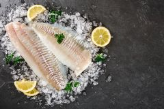 Fresh raw fillet white fish Pangasius with spices on ice over dark stone background.  Seafood, top view, flat lay, copy space. Fresh raw fillet white fish stock image