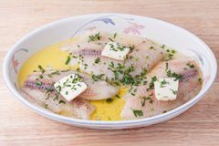 Fresh raw fish with butter, olive oil, lemon juice. Herbs and spices in baking dish Royalty Free Stock Photography
