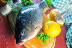 Fresh raw fish carp. On a wooden board in the kitchen Royalty Free Stock Photos