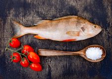 Fresh raw fish on a dark wooden background. River perch and spices.  stock photo