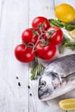 Fresh raw fish dorado. Fresh raw sea fish, decorated with lemon slices, herbs and tomatoes on a white wood background. Concept of healthy eating, top view Stock Photos