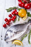 Fresh raw fish dorado. Fresh raw sea fish, decorated with lemon slices, herbs and tomatoes on a white wood background. Concept of healthy eating, top view Stock Image