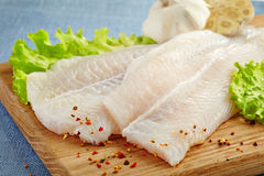 Fresh raw fish fillet. Fresh raw pangasius fish fillet on wooden cutting board Stock Image
