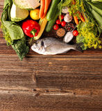Fresh raw fish and food ingredients on wooden background with em Stock Photos