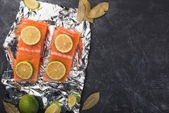 Sliced salmon fillet on a foil. Fresh raw fish with lime and spices on a baking tray. Metal black background Stock Image