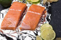 Sliced salmon fillet on a foil. Fresh raw fish with lime and spices on a baking tray. Metal black background Stock Photo