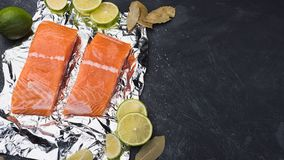 Sliced salmon fillet on a foil. Fresh raw fish with lime and spices on a baking tray. Metal black background Royalty Free Stock Image
