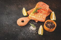 Fresh raw salmon steak fillet. Fresh raw fish salmon, steak fillet, with spices, lime, rosemary, salt, on a dark rusty background, copy space Royalty Free Stock Images