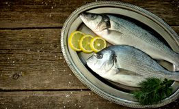 Fresh raw fish seabass and Dorado on an iron vintage tray and an old wooden background. Tasty food Stock Photo