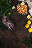 Fresh raw fish, shrimp, herbs with lemons and tablecloth. On dark table top Royalty Free Stock Photography