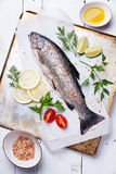 Fresh raw fish trout. With herbs and lemon on wooden background Stock Photography