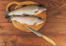 Fresh raw fish trout is two pieces on the board. For cutting food on a wooden table in rustic style near the knife Stock Images