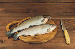 Fresh raw fish trout is two pieces on the board. For cutting food on a wooden table in rustic style near the knife Royalty Free Stock Image