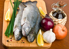 Fresh raw fish trout with vegetables. On a wooden board Stock Photos