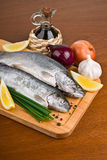 Fresh raw fish trout on a wooden board. Fresh raw fish trout with peppers, onions and lemon on a wooden board Stock Photography