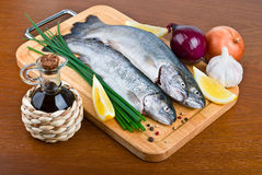 Fresh raw fish trout on wooden board. Fresh raw fish trout with oil, onions and lemon on a wooden background Royalty Free Stock Photo