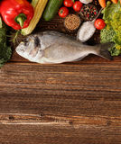 Fresh raw fish with vegetables on old wooden background. With space for text Stock Images