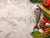 Fresh raw fish with vegetables on stone background. With space for text Royalty Free Stock Photo