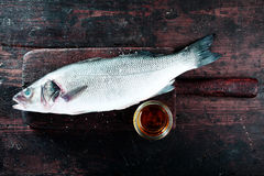 Fresh Raw Fish on Wood Board with Dish of Oil Stock Image