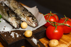 Fresh raw fish on wooden table. Fresh raw fish and ingridients on wooden table Royalty Free Stock Image