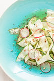 Fresh raw food diet salad close up. Zucchini 'tagliatelle', radish slices. Roasted sunflower seeds and vinaigrette dressing on blue plate from above Royalty Free Stock Photo