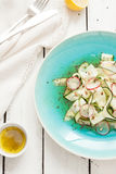 Fresh raw food diet salad - zucchini 'tagliatelle', radish slices, roasted sunflower seeds. And vinaigrette dressing on blue plate from above. White rustic Stock Photo
