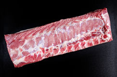 Fresh Raw French whole rack of pork striploin rindless on black board. Fresh Raw French whole rack of pork striploin rindless on black board Royalty Free Stock Images