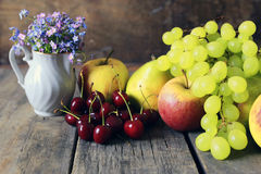 Fresh raw fruit on wooden background. Bright juicy ripe delicious fruit on an old wooden table Stock Image
