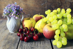 Fresh raw fruit on wooden background. Bright juicy ripe delicious fruit on an old wooden table Stock Photos