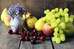 Fresh raw fruit on wooden background. Bright juicy ripe delicious fruit on an old wooden table Stock Photography