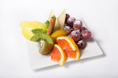 Fresh raw fruits. Sliced and served on a white plate Royalty Free Stock Photos
