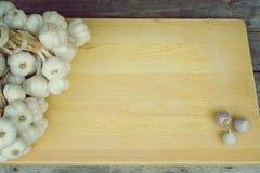 Fresh raw garlic bundle on cutting board, copy space, kitchen raw ingredient concept. Fresh raw garlic bundle on cutting board, kitchen raw ingredient concept Royalty Free Stock Photos
