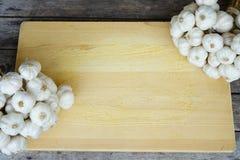Fresh raw garlic bundle on cutting board, copy space, kitchen raw ingredient concept. Fresh raw garlic bundle on cutting board, kitchen raw ingredient concept Royalty Free Stock Photo