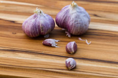 Fresh raw garlic. Close up of garden fresh raw garlic on a wooden cutting board Royalty Free Stock Photo