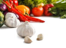 Fresh raw garlic with some vegetables at the background. Close up portrait of fresh raw garlic with some vegetables at the background  on white Royalty Free Stock Images