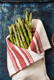 Fresh raw Green asparagus. In towel on blue wooden background Stock Photography