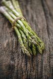 Fresh raw green asparagus. On wooden bark background Royalty Free Stock Photo